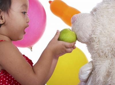 niña alimentando a osito con manzana